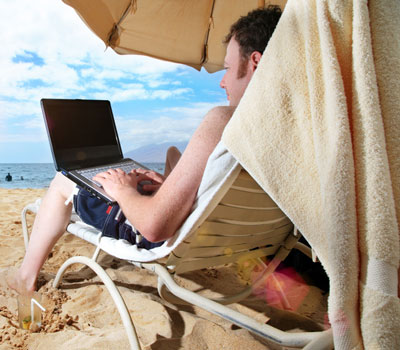 Photo of a man working on a laptop computer while at the beach