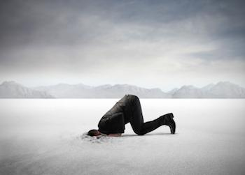 Male in a business suit with his head buried in the sand