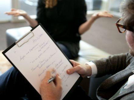 Ein Mann macht sich Notizen, während eine Frau spricht.