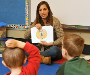 SUNY Oswego senior psychology major Holly Santimaw shows a picture of a child in a bubble of personal space to reinforce a social-skills lesson for pre-kindergarteners in Margaret Talamos class at Minetto Elementary School. The lesson was part of a project in Oswego schools directed by Matthew Dykas of the college's psychology department and staffed by interns.