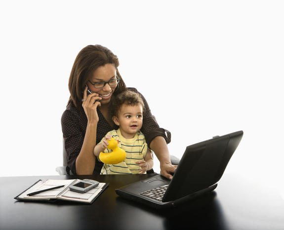 A woman sits at a computer with a toddler on her lap